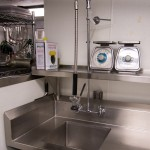 "A washing station. In a large restaurant like this, things get washed as they get used otherwise they would be constantly running out of trays and plates and the like. It is an important bottleneck in the kitchen... ""if a dishwasher calls in sick... everyone's in trouble"""